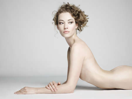 nude sexy beautiful woman with long stylish hairstyle pose on white background in photostudio. Erotic portrait of elegant nude lady with perfect naked body. Sexual photography of young nude blonde. Sensual model with long hair sits in studio. Pretty strip