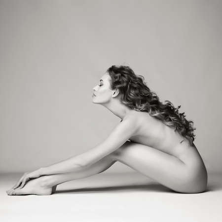 nude sexy beautiful woman with long stylish hairstyle pose on white background in photostudio. Erotic portrait of elegant nude lady with perfect body. Sexual photography of young nude blonde. Sensual model with long hair sits in studio. Pretty stripper show her figure without clothes. Lovely professional photo-model with hot hips lies on gray background. Fashion image of young girl with modern makeup.