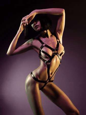 sexy young woman in erotic fetish wear dancing striptease in nightclub. Beautiful nude body of sensuality elegant lady. Lizenzfreie Bilder
