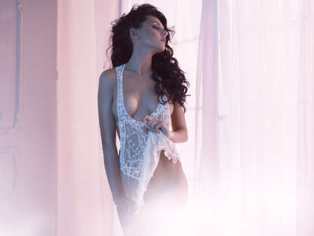 Art boudoir fashion photo of beautiful gorgeous woman in lingerie at the window. Perfect body. Beauty and health