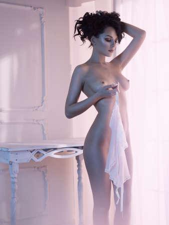 Art boudoir Mode Foto von schönen wunderschönen Frau in Dessous am Fenster. Perfekter Körper. Schönheit und Gesundheit