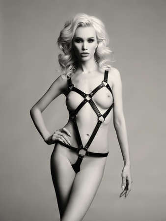 Schwarzweiss-Studiomodefoto der nackten eleganten Frau in provozierendem ledernem Schwertgurt. Fetisch Dessous