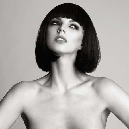 Black and white Fashion photo of beautiful elegant woman with short haircut. Brunette bob hairstyle. Makeup, Health and Beauty