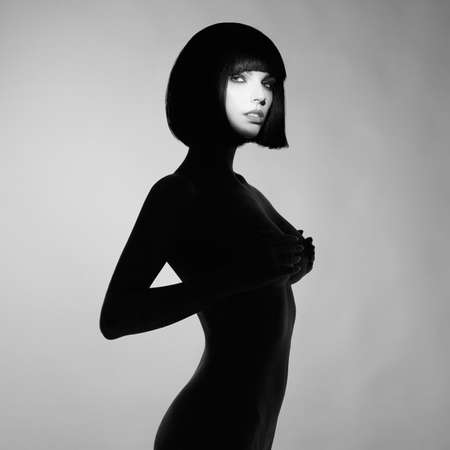 Black and white concept fashion photo of nude elegant woman wearing shadow. Brunette bob hairstyle. Fashion, Health and beauty Standard-Bild