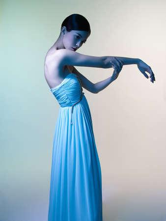 Fashion studio portrait of beautiful woman in azure dress on colorful background. Asian beauty.