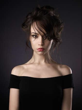 Het portret van de studiokunst van mooie vrouw met elegant kapsel op zwarte achtergrond