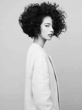 Studio fashion portrait of beautiful asian woman in white coat on gray background. Stylish look book. Autumn Winter season.