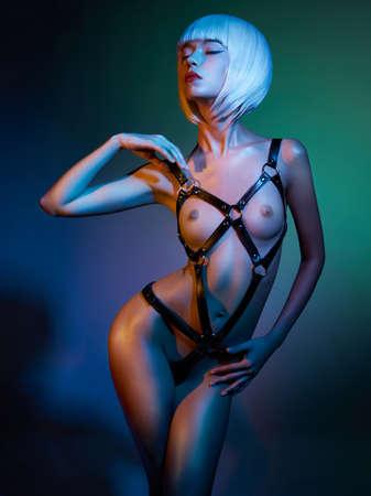 sexy young woman in erotic fetish wear dancing striptease in nightclub. Beautiful nude body of sensuality elegant lady.