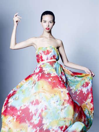 Fashion studio portrait of beautiful woman in azure flowing dress on colorful background. Asian beauty. Standard-Bild