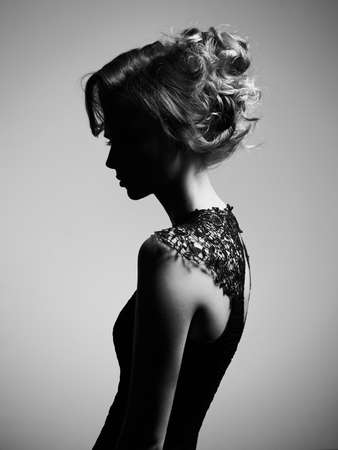 Studio fashion photo of beautiful young lady on gray background. Classic studio portrait. Elegant hairstyle
