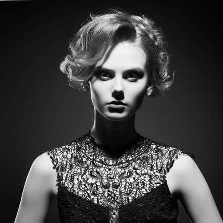Studio fashion photo of beautiful young lady on black background. Classic studio portrait. Elegant hairstyle Standard-Bild