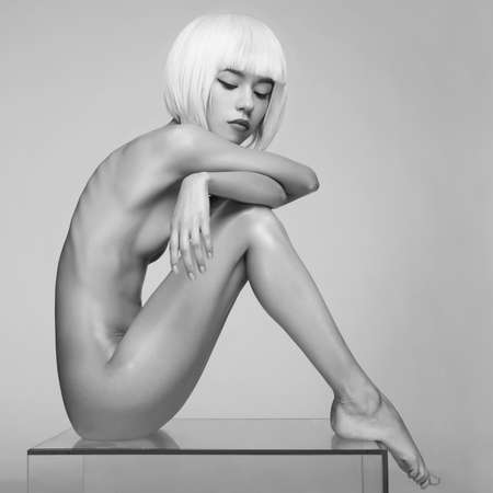 Nude sensual woman with fashionable hairstyle on white background. Beautiful naked lady. Beautiful modern makeup.