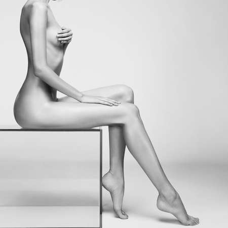 nude sexy beautiful woman with perfect figure pose on white background in photostudio. Erotic portrait of elegant nude lady with  naked body. Sexual photography of young nude blonde. Sensual model. Lovely professional photo-model with hot hips lies on gray background. Standard-Bild