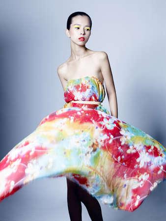 Fashion studio portrait of beautiful woman in azure flowing dress on colorful background. Asian beauty. Stockfoto