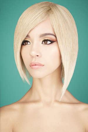 ブロンドの短い髪を持つ素敵なアジアの女性のファッションスタジオの肖像画。ファッションと美しさ。明るいメイク。ファッショナブルなヘアカ