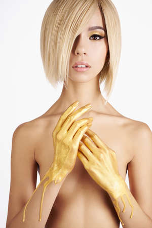 Fashion art studio photo of elegant nude asian woman with gold flowing down her hands. Fashion and beauty. Conceptual image. Bright makeup                      Standard-Bild
