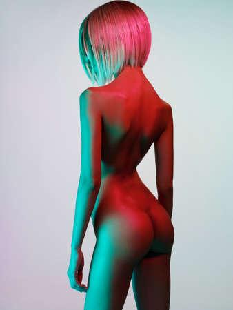 Fashion art studio photo of elegant nude model in the light colored spotlights. Fashion and beauty. Conceptual image. Metallic art, body art. Slim, fit woman. Gold skin