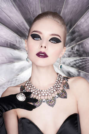 Fashion studio photo of beautiful elegant woman with bright makeup and with set jewelry. Fashion arrow shape. Woman in necklace with ring and earrings. Glamorous Gatsby style Banco de Imagens