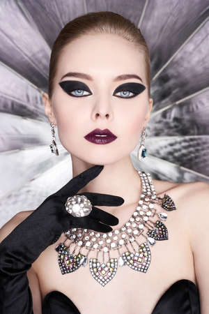 Fashion studio photo of beautiful elegant woman with bright makeup and with set jewelry. Fashion arrow shape. Woman in necklace with ring and earrings. Glamorous Gatsby style Stock Photo