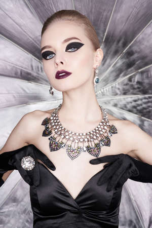 Fashion studio photo of beautiful elegant woman with bright makeup and with set jewelry. Fashion arrow shape. Woman in necklace with ring and earrings. Glamorous Gatsby style 스톡 콘텐츠