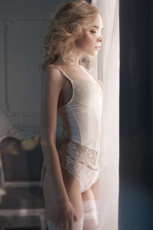 Fashion art photo of beautiful sensual woman in white lingerie at the window. Home interior. Beautiful morning