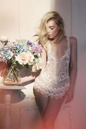 Fashion art photo of beautiful sensual woman in white negligee with flowers in light interior. Home interior. Beautiful morning                               Stock Photo