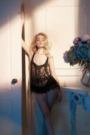 Fashion art photo of beautiful sensual woman in blac negligee with flowers in light interior. Home interior. Beautiful morning Banco de Imagens - 101869654