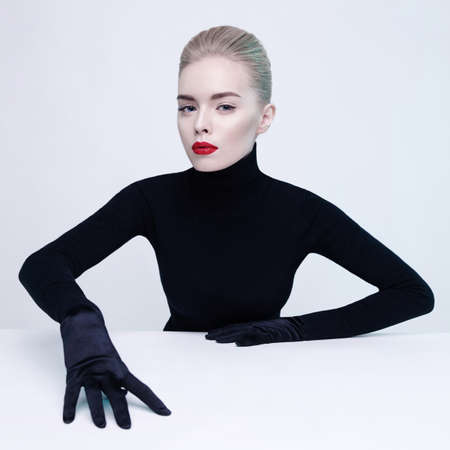 Conceptual fashion studio portrait of beautiful blonde woman in black turtleneck with perfect makeup. Red lips. Strobing