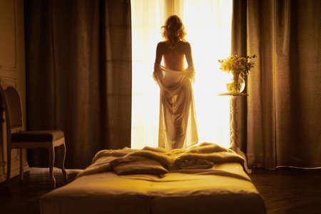Lifestyle art photo of beautiful sensual woman at the window. Home interior. Beautiful morning. Woman dress up
