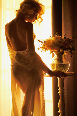 Lifestyle art photo of beautiful sensual blonde with flowers at the window. Home interior. Beautiful morning Stock Photo