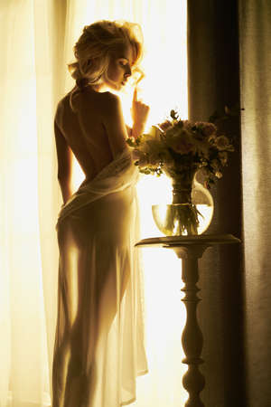 Lifestyle art photo of beautiful sensual blonde with flowers at the window. Home interior. Beautiful morning Banque d'images