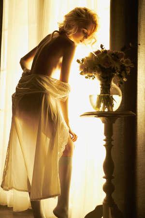 Photo d'art de style de vie d'une belle blonde sensuelle avec des fleurs à la fenêtre. Intérieur de la maison. Belle matinée
