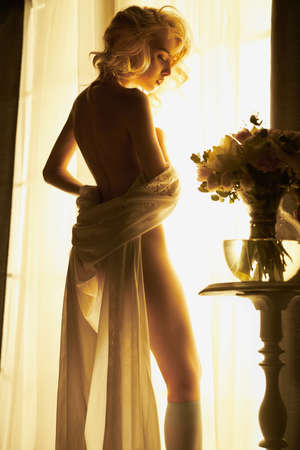 Lifestyle art photo of beautiful sensual blonde in white lingerie with flowers at the window. Home interior. Beautiful morning
