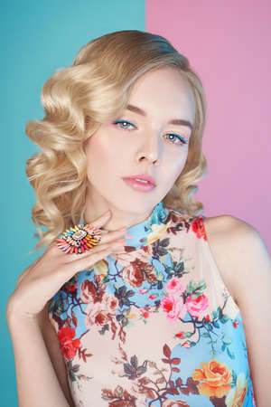 Fashion studio portrait of beautiful blonde woman with color makup on colorful background.  Perfect makeup in pastel shades. Hairstyle Hollywood wave Stock Photo