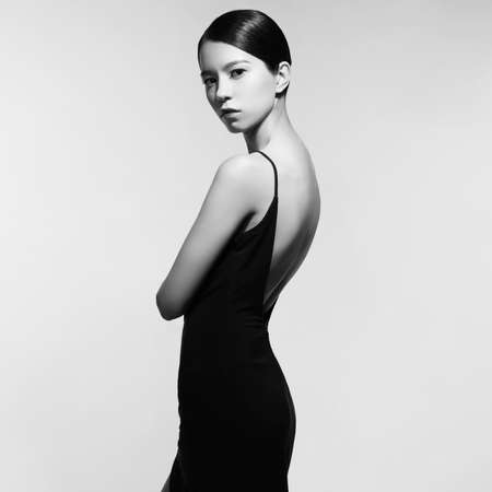 Fashion studio portrait of beautiful woman in black evening dress. Asian beauty.