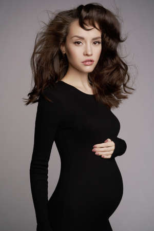 Studio fashion portrait of beautiful pregnant woman in black dress. Happy pregnancy. Beauty and health