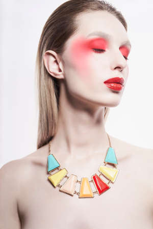 Studio portrait of sexy lady with blonde hair. Woman posing in colorful neacklace . Beautiful girl with bright makeup. Portrait with mirrrors.