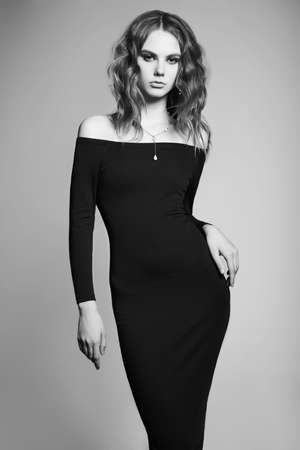Fashion studio portrait of young womanin black dress. Beautiful lady with curly hair. Black and white photo. Stock fotó
