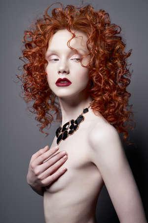 Hermosa mujer joven con joyas negras y pelo rojo sobre fondo gris. Señora bonita desnuda con lápiz labial rojo brillante y maquillaje de arte moderno. Pose de modelo sensual en estudio fotográfico. Cuerpo sexy.
