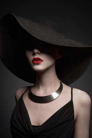 Retrato de moda de dama joven con hermoso sombrero negro y vestido de noche. Mujer elegante con estilo con joyería moderna. Foto de estudio de modelo bonita sobre fondo gris. Foto de archivo