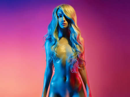 Nude beautiful blonde dancing in colorful light. Erotic portrait of sexy woman with long hairs. Sexual naked model pose on pink background. Perfect female body of elegant stripper. Pretty girl.