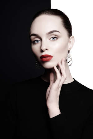 young lady with big stylish bijouterie in black-and-white studio. beautiful woman with perfect lips and red lipstick pose in photostudio. Fashion portrait of fashionable model.