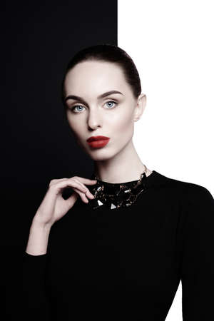 young sexy lady with black stylish bijouterie in black-and-white studio. beautiful woman with perfect lips and red lipstick pose in photostudio. Fashion portrait of fashionable model.