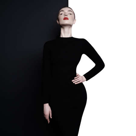 Fashion art studio portrait of elegant woman in geometric black and white background. Professional makeup with red lipstick. Stylish classic dress.