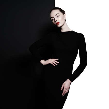 Ritratto in studio d'arte di moda di donna elegante in sfondo bianco e nero geometrico. Trucco professionale con rossetto rosso. Abito classico alla moda.