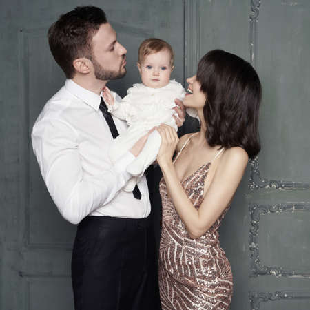 Young family with beautiful little baby in thair arms. Fashion portrait of two parents with pretty daughter. Stylish mom and dad in evening dress and small girl in white sliders. Studio portrait.