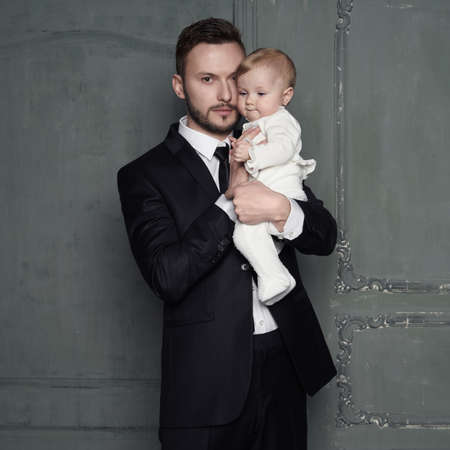 Young father with beautiful little baby in his arms. Fashion portrait of man with pretty daughter. Stylish dad in evening black suit and small girl in white sliders. Studio portrait.