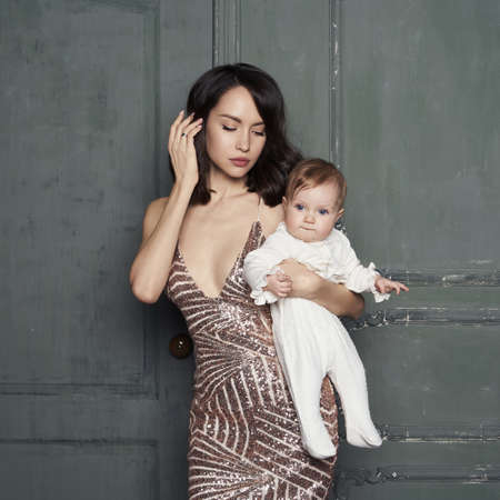 Young mother with beautiful little baby in her arms. Fashion portrait of lady with pretty daughter. Stylish mom in evening dress and small girl in white sliders. Studio portrait. 版權商用圖片