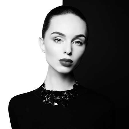 young sexy lady with black stylish bijouterie in black-and-white studio. beautiful woman with perfect lips and black lipstick pose in photostudio. Fashion portrait of fashionable model.