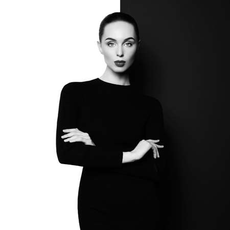 Fashion art studio portrait of elegant woman in geometric black and white background. Professional makeup with black lipstick. Stylish classic dress. 版權商用圖片